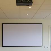 Ljudabsorbent på vägg som fungerar som projektionsduk