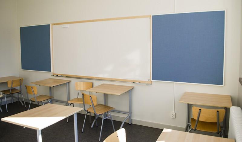 Väggabsorbenter bredvid whiteboard i ett klassrum.