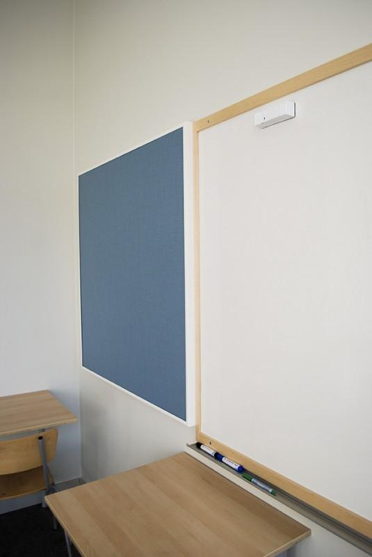 Väggabsorbent bredvid whiteboard i ett klassrum.